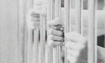 Hand on prison bars
